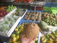 Enjoying a fresh coconut at the fruit and vegetable stand.